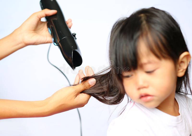 Mother drying hair of her child girl on white background royalty free stock photos