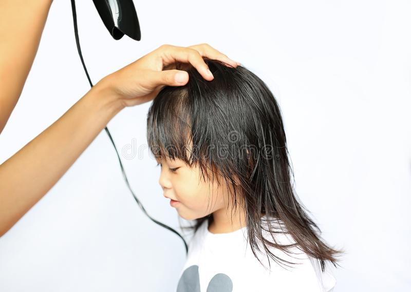Mother drying hair of her child girl on white background stock photo