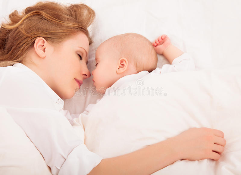 Mother embraces the newborn baby sleeping together in bed. Happy family sleeping together. mother embraces the newborn baby in bed royalty free stock photography