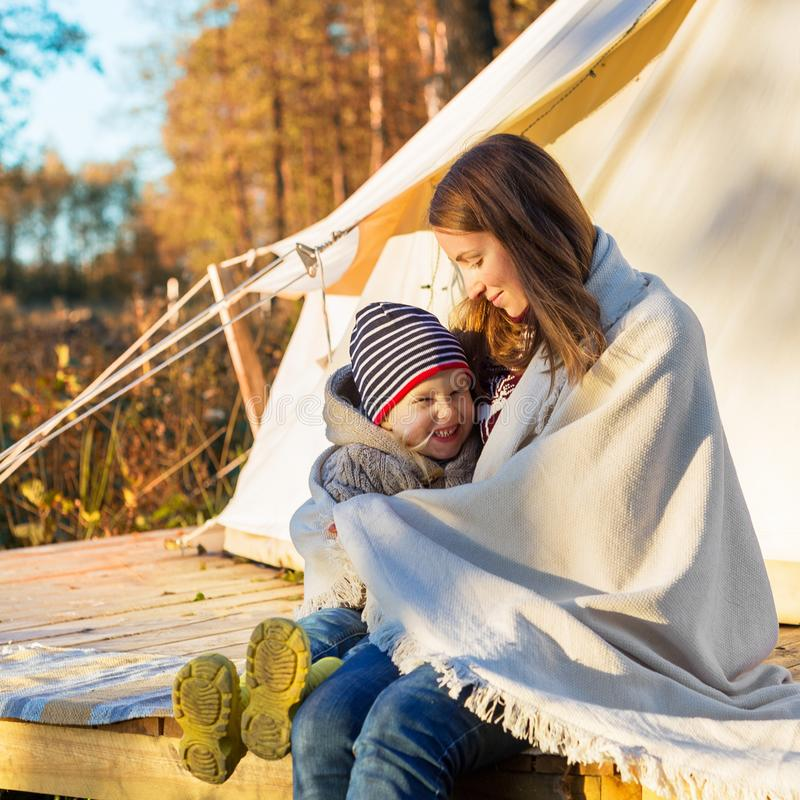 Happy mother embracing her kid with a blanket while sitting near canvas tent royalty free stock photo