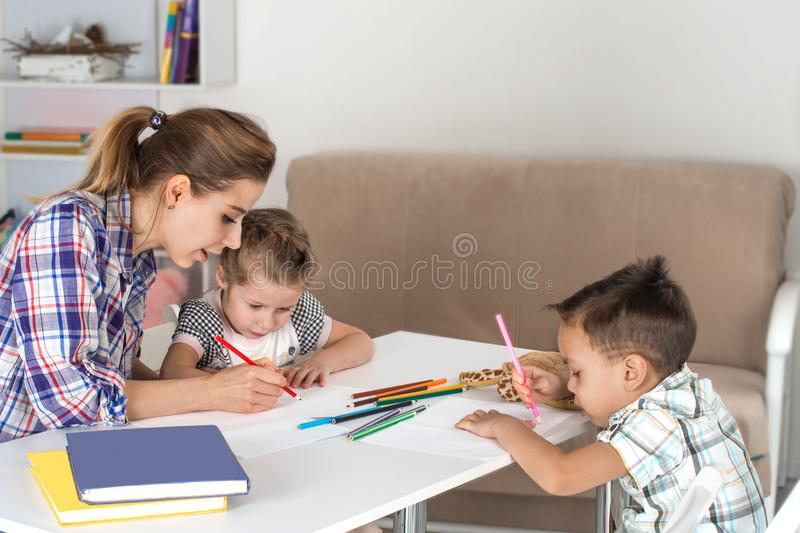 Mother is engaged with children. She draws together with the daughter and the son. stock photography
