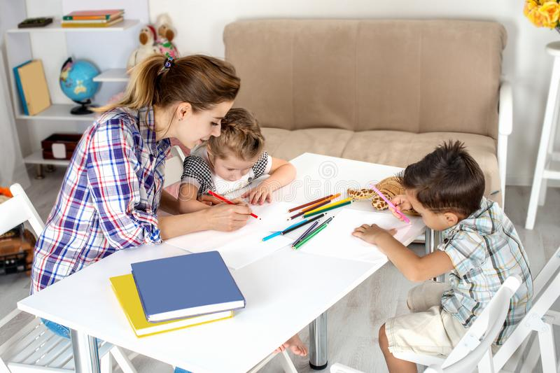 Mother is engaged with children. She draws together with the daughter and the son. stock image