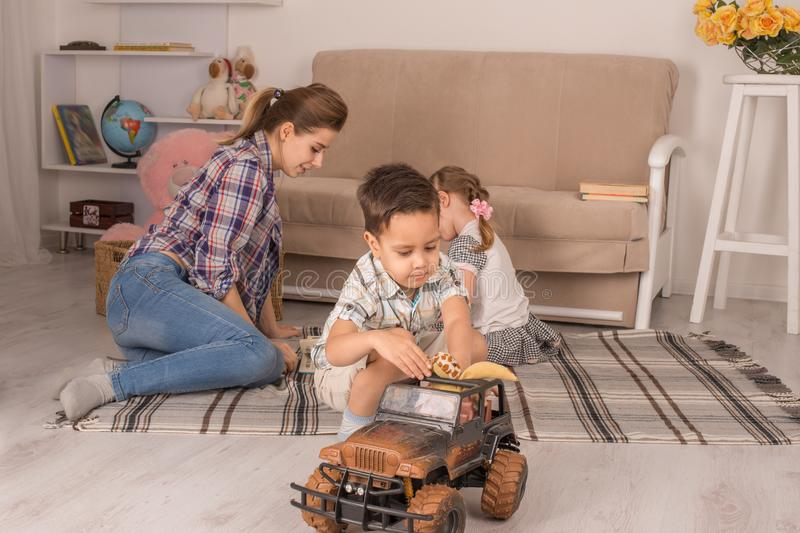 Mother is engaged with children. Mother with small children play on the floor. Son plays with toy car royalty free stock photography