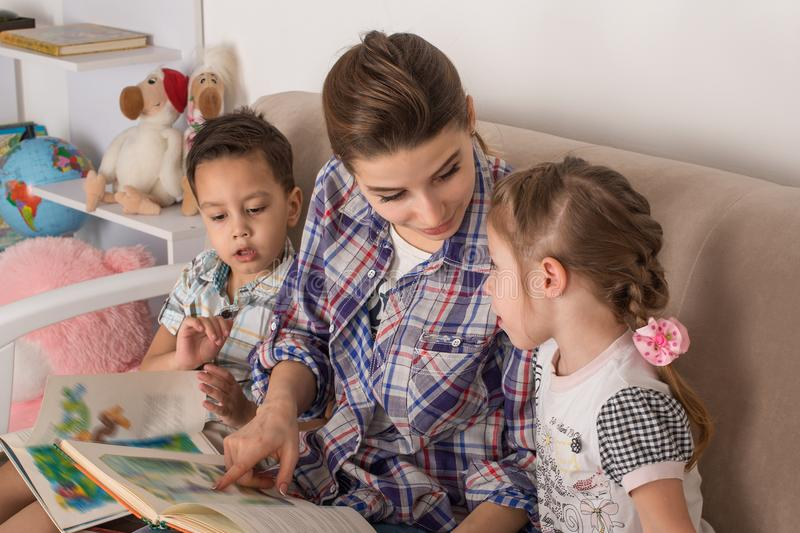 Mother is engaged with children. Mother with small children read. Books royalty free stock image