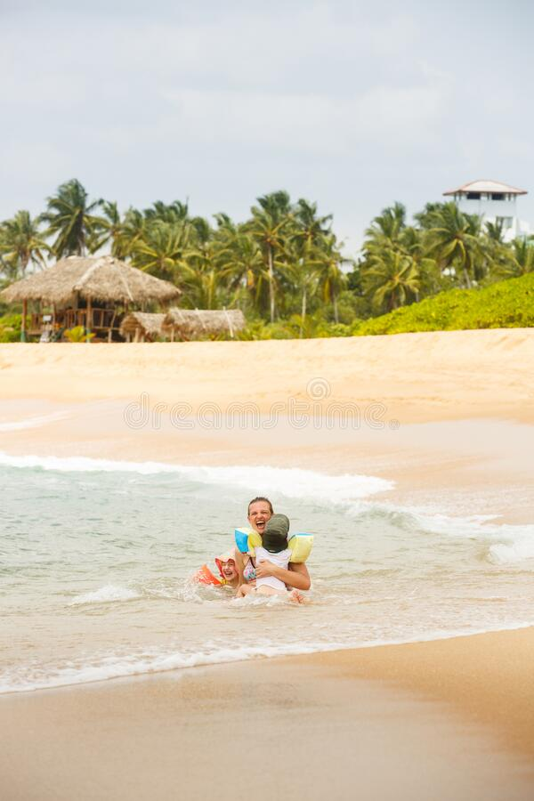 Mother enjoying a tropical beach, playing in the waves with her children royalty free stock photography