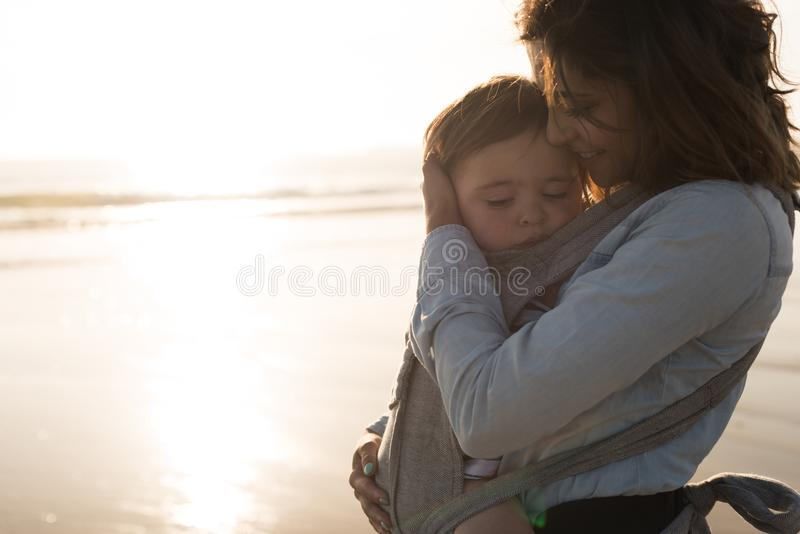 Mother carrying baby stock image
