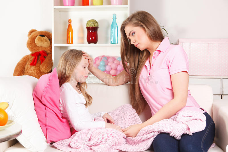 Mother examining child's fever royalty free stock photos
