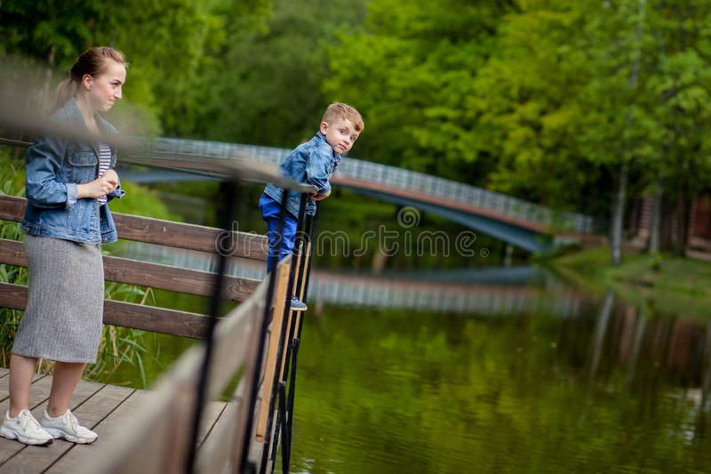Mother is experiencing that the child will fall into the water. A little boy climbs a bridge railing in the park. The threat of. Drowning. Danger to children royalty free stock photos