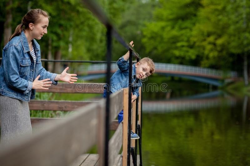 Mother is experiencing that the child will fall into the water. A little boy climbs a bridge railing in the park. The threat of. Drowning. Danger to children stock photos