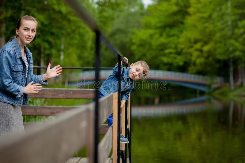Mother is experiencing that the child will fall into the water. A little boy climbs a bridge railing in the park. The threat of. Drowning. Danger to children royalty free stock images