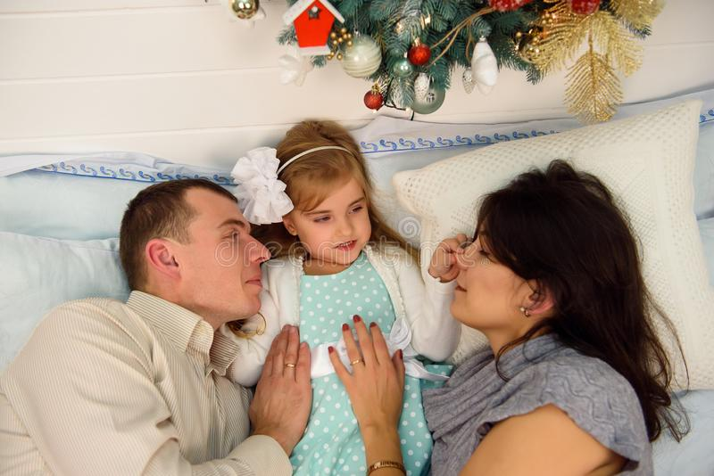 Mother, father and baby having fun in bedroom. People relaxing at home. Winter holiday Xmas and New Year concept. royalty free stock photos
