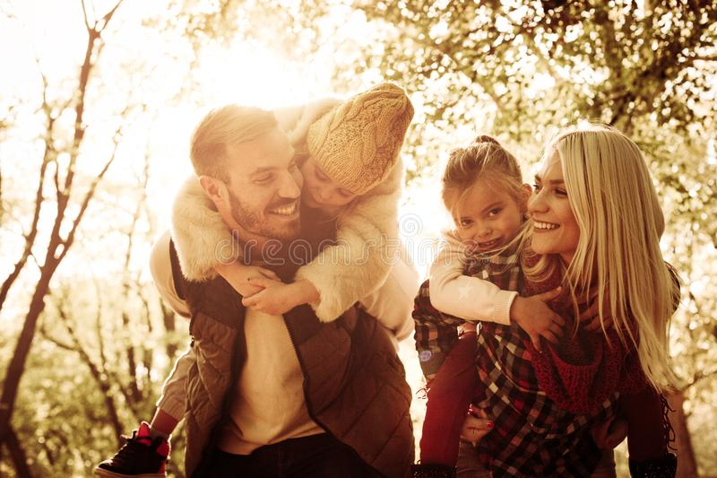Mother and father carrying their daughters on piggyback. royalty free stock photography