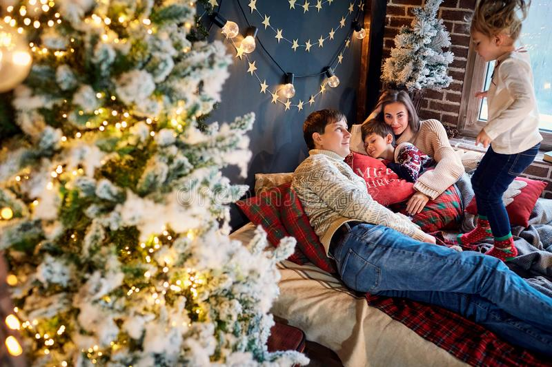 Mother and father with children playing at home on Christmas Day stock images