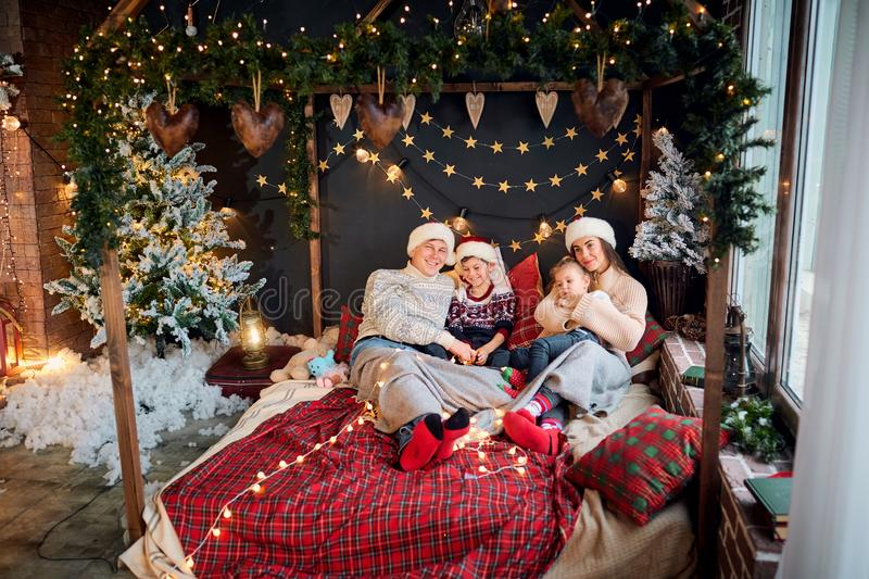Mother and father with children playing at home on Christmas Day royalty free stock image