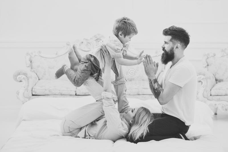 Mother and father cuddling with cute son. Young family spend time together on bed, luxury interior background. Parents royalty free stock images