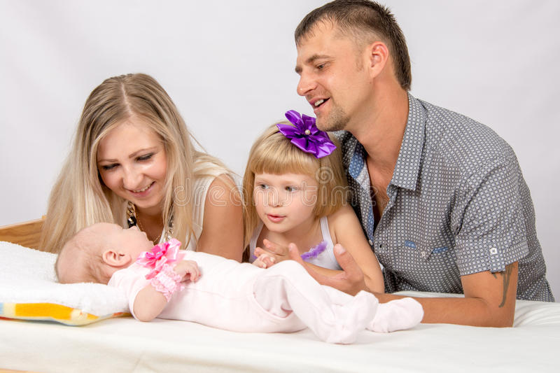 Mother, father and daughter is considering a five-year new-born baby. Young parents and daughter sit at the five-year crib, the crib is on a two-month baby on royalty free stock images