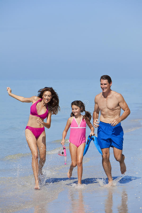 Mother, Father & Daughter Family Running on Beach royalty free stock images