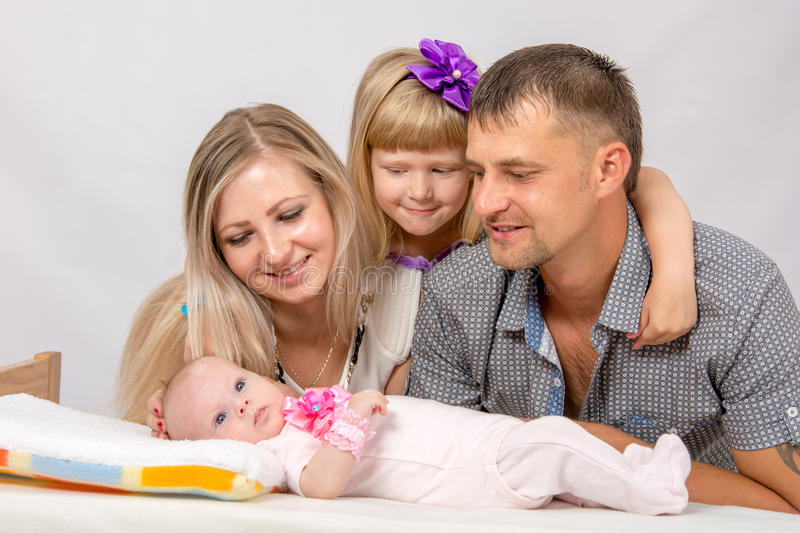 Mother, father and daughter, five-year look at newborn baby. Young parents and daughter sit at the five-year crib, the crib is on a two-month baby on her back royalty free stock photos
