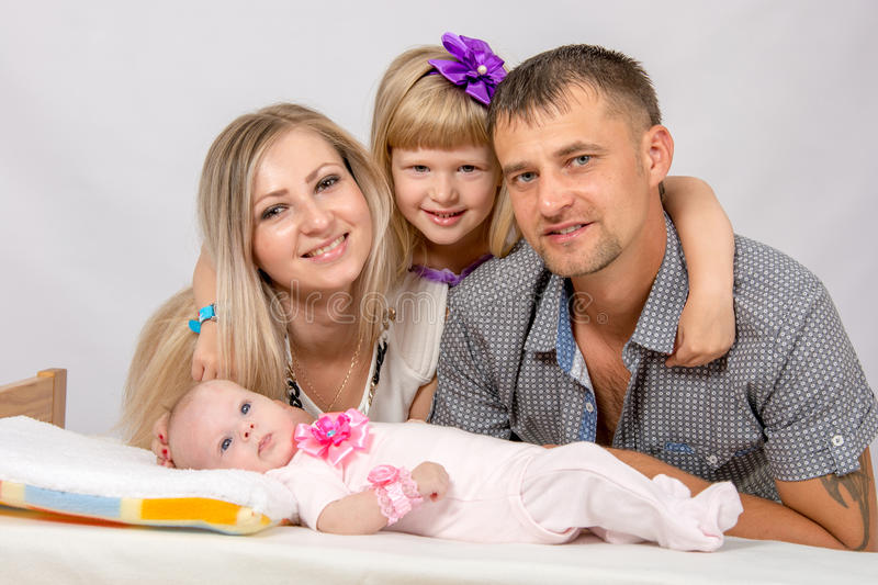 Mother, father, daughter and five-year newborn baby looks in the picture. Young parents and daughter sit at the five-year crib, the crib is on a two-month baby stock images