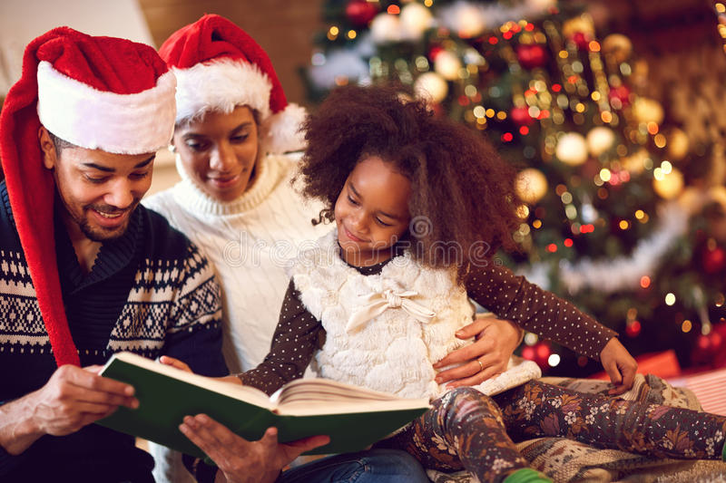 mother, father and daughter read a book at fireplace on Christmas . stock photo