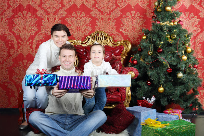 Mother, father and daugther give gifts near Christmas tree. At home royalty free stock photos