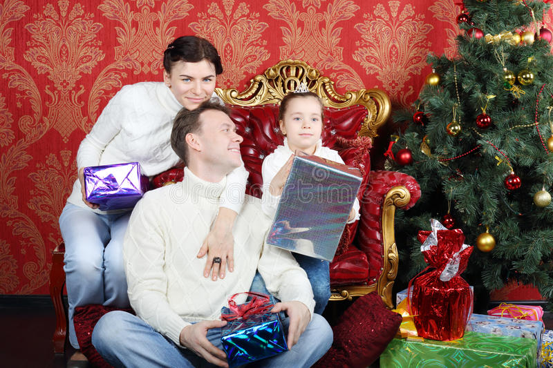 Mother, father and daugther hold gifts near Christmas tree. At home, men looks at girl royalty free stock image