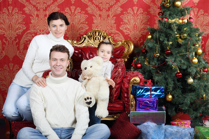 Mother, father and daugther with teddy bear and smile. Near Christmas tree at home royalty free stock photo