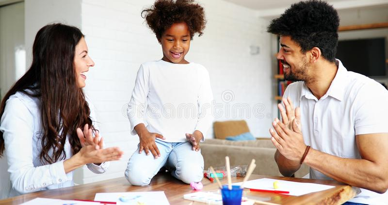 Mother and father drawing together with their child stock images