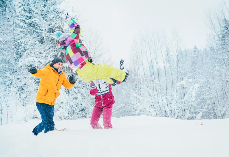 Mother and father family fooling in snow forest by throwing their little daugher to snowdrift royalty free stock images