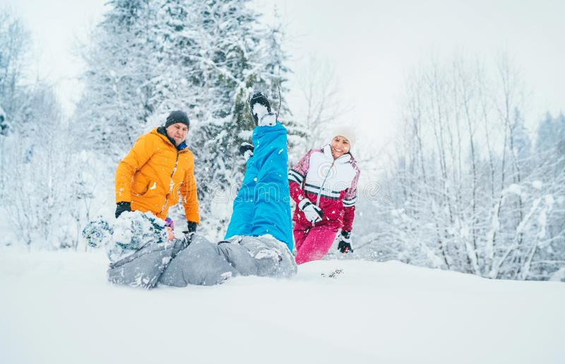 Mother and father family fooling in snow forest by throwing their little son to snowdrift stock image