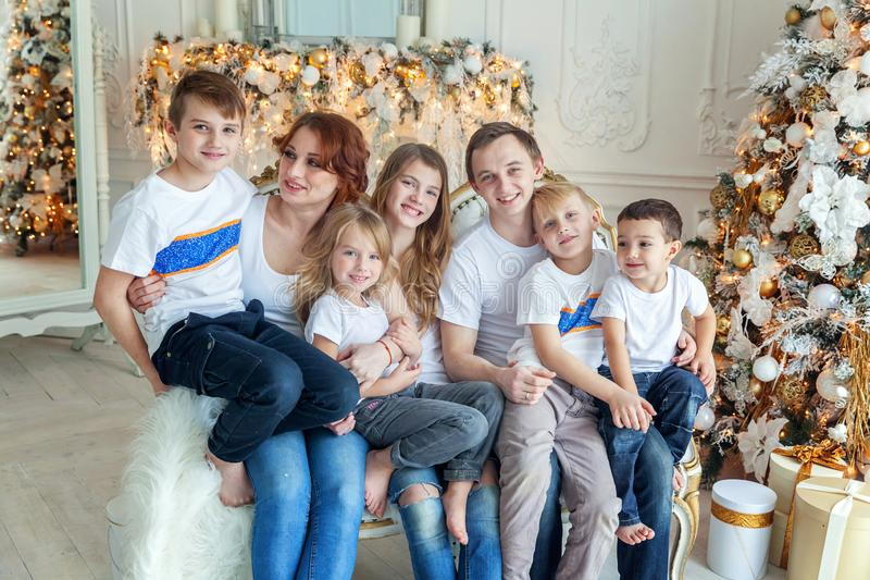 Mother father and five children near Christmas tree at home stock images