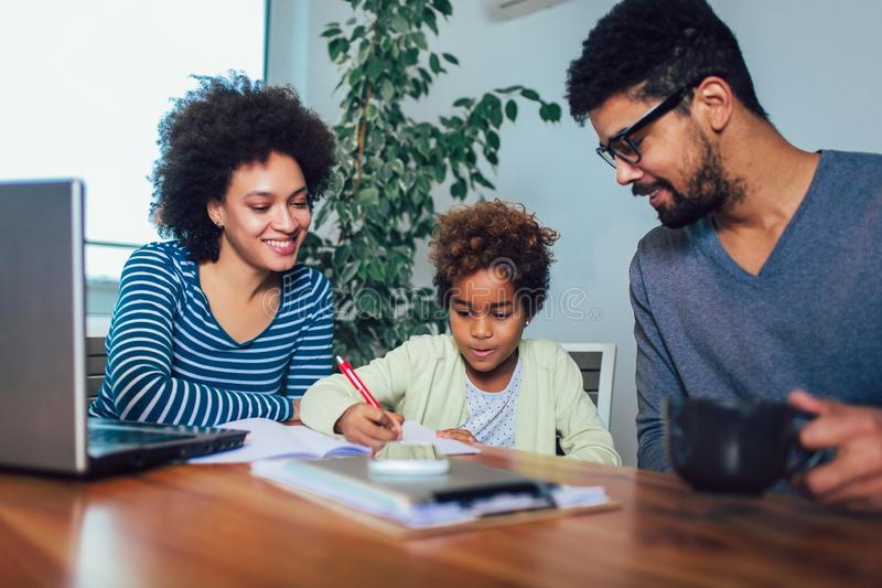 Mother and father helping daughter to do homework learning to calculate stock photo