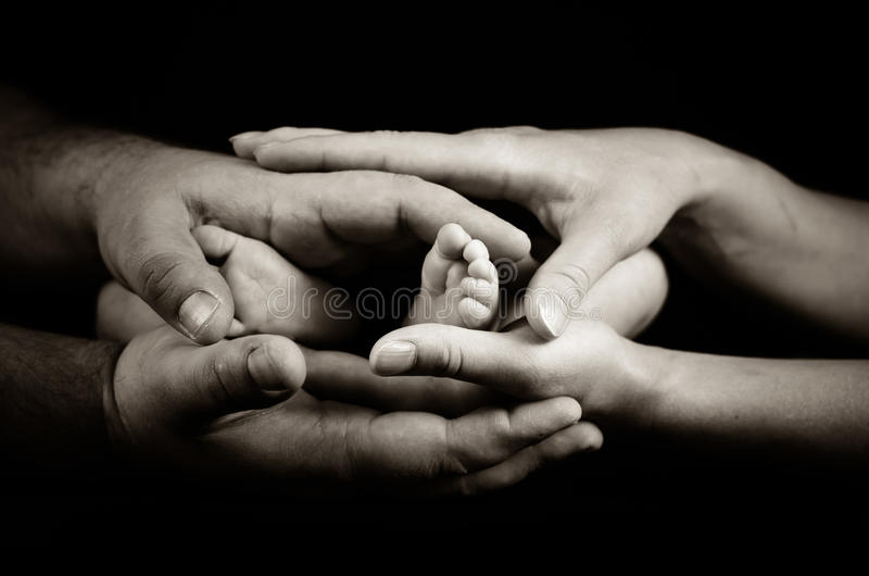 Mother and father holding little newborn's feet. Mother and father holding with love little newborn's feet. Black and white photography royalty free stock photography
