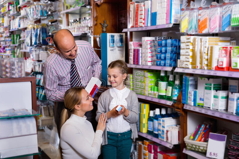 Mother and father with kid picking a article in pharmaceutical s royalty free stock photos