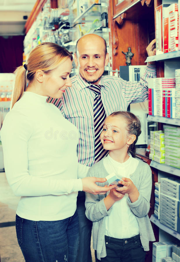 Mother and father with kid picking in pharmaceutical store stock image