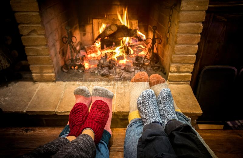 Mother father and kids sitting at cosy fireplace on Christmas time - Lovely family resting together on woolen socks at home fire stock images
