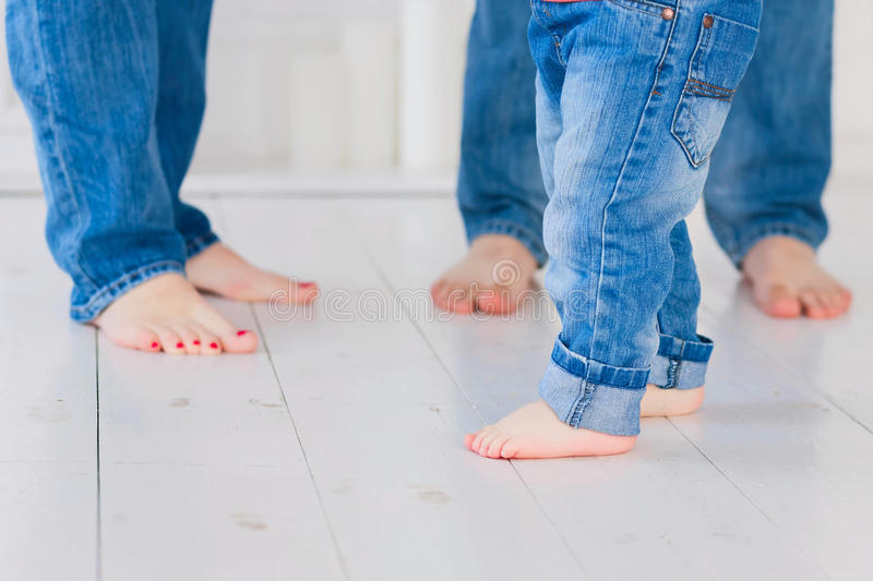 Mother, father and little child wearing blue jeans, barefoot. Fo stock photography