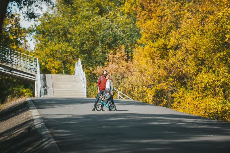Mother, father and little son on bike poses in autumn park at the distance in the sunny day stock images