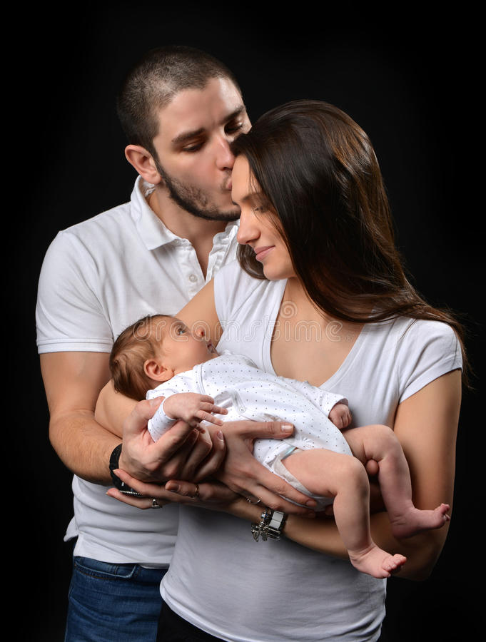 Mother and father smiling holding their newborn infant child baby boy stock photography