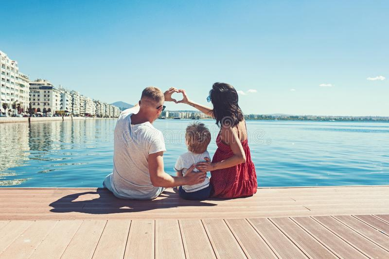 Mother and father with son form heart of hands. Family travel with kid on mothers or fathers day. Summer vacation of stock photography