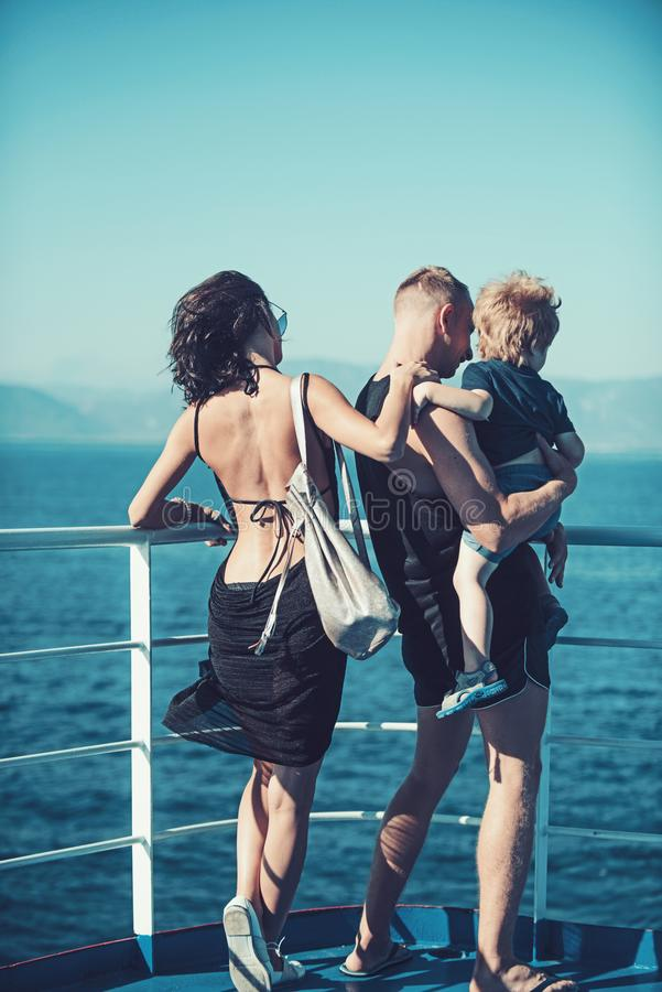Mother and father with son look at sea on beach. Summer vacation of happy family. Family travel with kid on mothers or stock photos