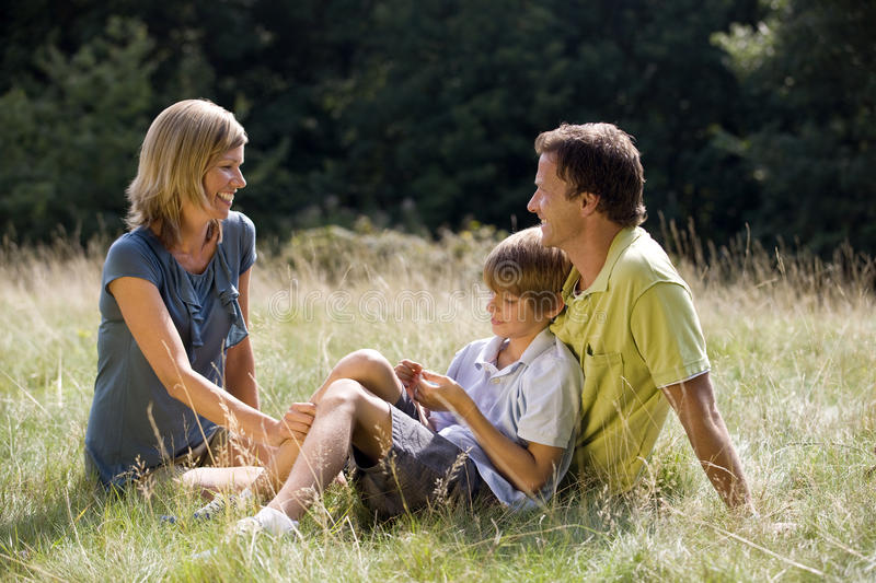 Mother, father and son sitting on the grass stock photo