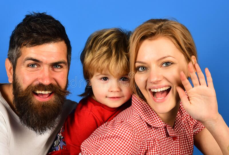 Mother, father and son with smiling faces hug on blue stock photography