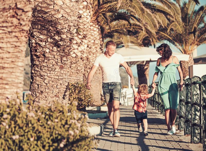 Mother and father with son walk at beach palms. Summer vacation of happy family. Love and trust as family values. Child. With father and mother. Family travel stock photo