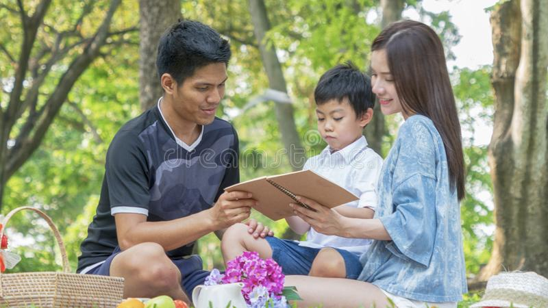 mother and father are teaching kid in park with book.Happy family picnic concept. stock photo
