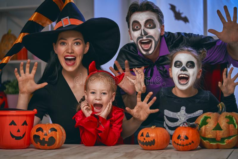 Family celebrating Halloween. Mother, father and their kids having fun at home. Happy family celebrating Halloween. People wearing carnival costumes and makeup royalty free stock photos