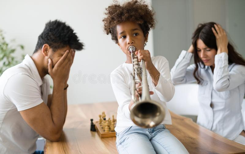 Mother and father trying to play chess while their child plays trumpet stock images