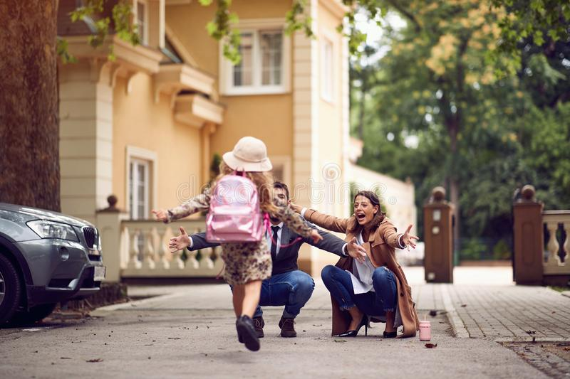 Mother and father waiting their schoolgirl at after class at first day of school. Happy mother and father waiting their schoolgirl at after class at first day of royalty free stock photo