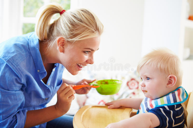Mother Feeding Baby Boy In High Chair stock images