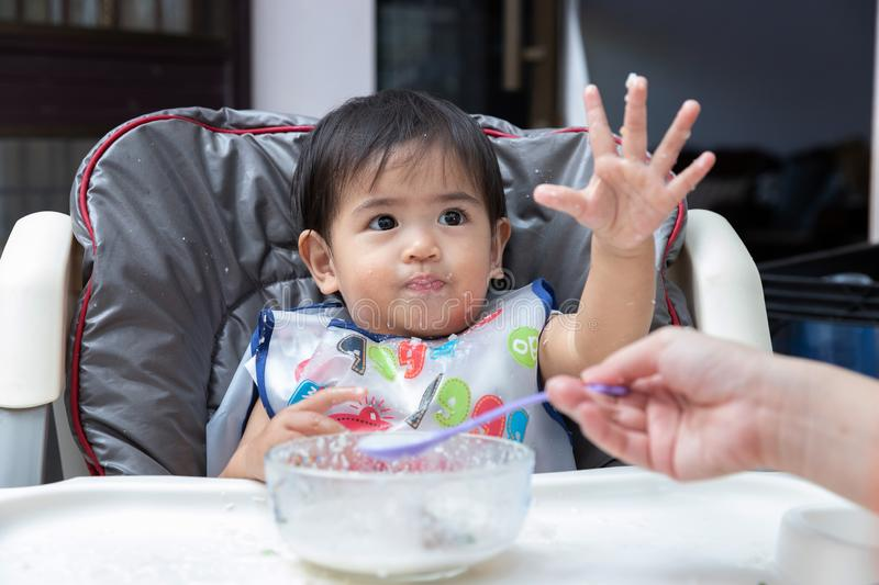 Mother feeding baby food to her child stock photo